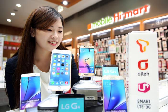 20% 선택약정 요금할인을 선택하는 사람이 크게 늘고 있다. 롯데하이마트에서 고객이 최신 프리미엄폰을 살펴보고 있다.