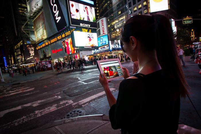 옥외 디지털 사이니지가 설치된 도심에서 사용자가 태블릿PC를 통해서 디지털 마케팅 광고를 시청하고 있다. <전자신문DB>