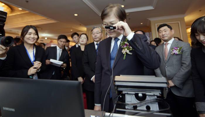 최양희 미래부 장관이 전시박람회에서 이리언스의 홍체인식기술을 체험하고 있다.(사진=미래부 제공)