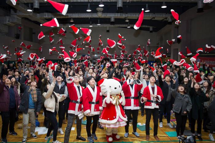 12일 산타학교에서 열린 사랑의 몰래산타 준비 행사에 참가한 자원봉사자 1000여명이 헬로키티 산타와 산타 모자를 위로 던지고 있다. <사진=산리오코리아>