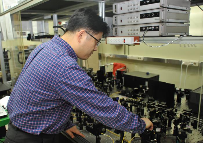 박희수 표준과학연구원 연구원이 광자 큐비트 실험 장비를 점검하고 있다.