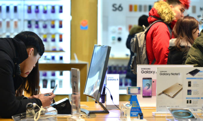 지난 달 26일 서울 서초동 삼성전자 딜라이트숍에서 고객이 삼성 휴대폰을 체험하고 있다.<br />윤성혁기자 shyoon@etnews.com