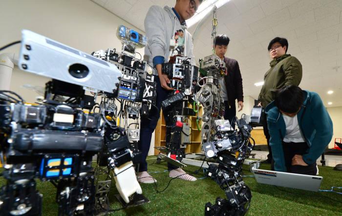 국민대 로봇제어연구실 학생들이 인공지능 SW를 축구로봇에 적용해 시연하고 있다. 윤성혁기자 shyoon@etnews.com
