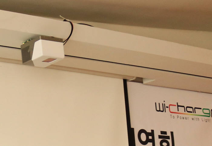 시연회장 천장에 달린 트랜스미터(송전기)가 스마트폰 등에 장착된 리시버(수신기)를 통해 충전을 가능하게 한다.