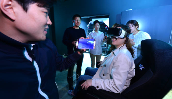CJ4D플렉스가 영화의 장면에 맞춰 움직이는 모션 시트와 더불어 바람, 빛, 안개, 향기, 진동 등을 체감하는 4DX 기기에 VR을 더한 새로운 영상시스템을 선보였다. 본지 콘텐츠 담당 김시소 기자(맨 왼쪽)가 VR을 착용한 4DX 기기 시승자의 반응을 살피고 있다. 윤성혁기자 shyoon@etnews.com