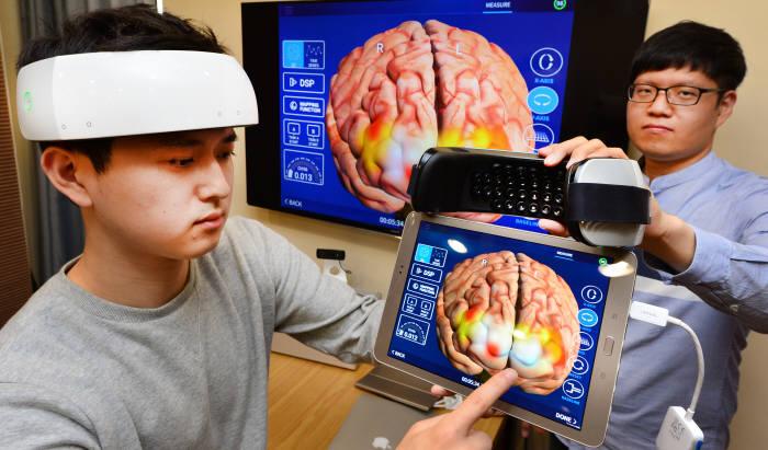17일 오비이랩 연구원이 실시간 뇌 활동을 측정할 수 있는 초소형 근적외선 뇌 영상장치 `널싯`을 시연하고 있다. 윤성혁기자 shyoon@etnews.com