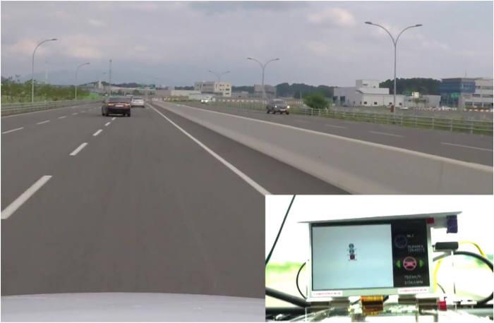 V2X 실차 테스트 모습. 차량 내 단말기가 V2X 통신으로 전방 검은색 차량 앞 비상정지 차량을 표시하고 있다.