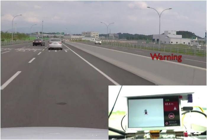 V2X 실차 테스트 모습. 차량 내 단말기가 V2X 통신으로 전방 검은색 차량 옆 비상정지 차량을 표시하고 있다. 정지 차량과 거리가 가까워지자 경고를 보내고 있다.