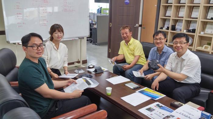정철호 대표(오른쪽)와 제이엔디 임직원이 스마트 주차 안내 시스템 개발 관련 회의를 하고 있다.