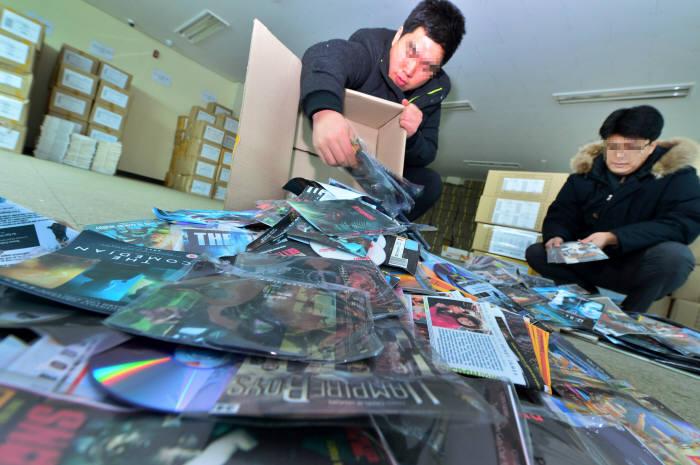 2013년 한국저작권단체연합회 저작권보호센터 단속 요원들이 수거한 불법 영화, 음반 등을 분류하고 있다.