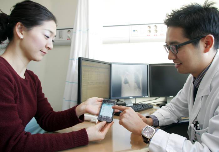 의사가 스마트폰에 저장된 정보를 활용해 진료 중이다.