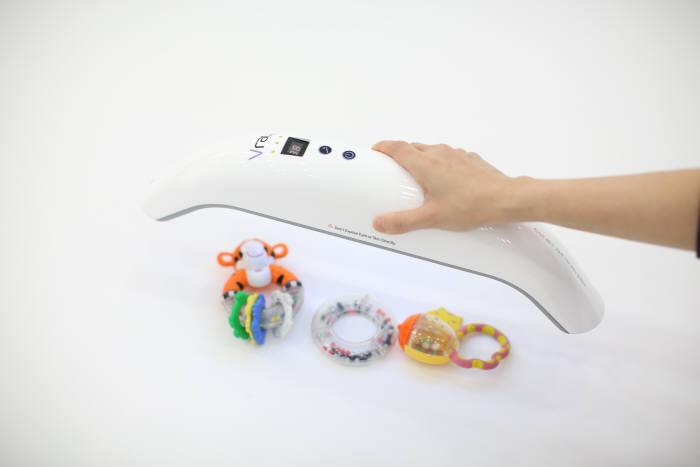 프라임테크의 살균기 `브이레이`로 장난감을 살균하는 모습