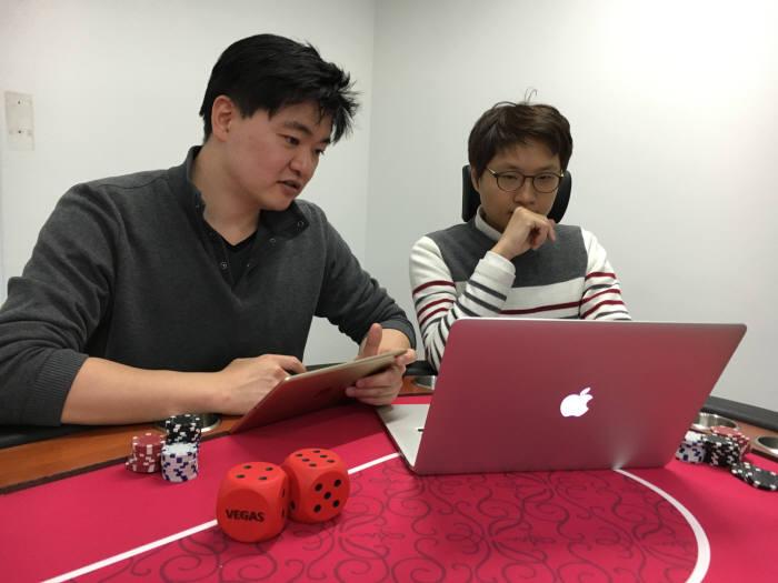 윤일환(왼쪽), 김준영 베이글코드 대표가 베가스파티슬롯을 시연 중이다.
