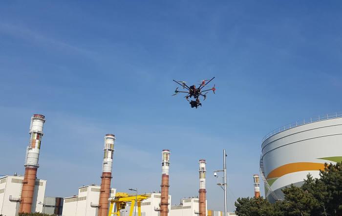 드론이 한국서부발전 발전소 연돌(굴뚝) 상부를 점검하기 위해 날아오르고 있다.