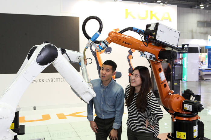 대기업들은 생산품질을 좌우할 수 있는 정밀도와 안전성, 확장성 등이 검증된 외산 산업용 로봇을 도입하기가 쉽다. 하지만 자본력과 시장성이 부족한 중소기업에게 산업용 로봇은 쉽사리 선택하기 어렵다. 해외업체 쿠카의 로봇시연을 보고 있는 관람객들. (사진=전자신문DB)