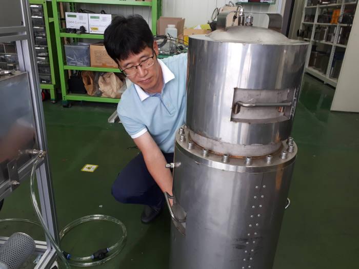 김홍석 한국기계연구원 그린동력연구실 책임연구원이 암모늄을 이용한 NOx 저감에 쓰이는 장비를 살펴보고 있다.