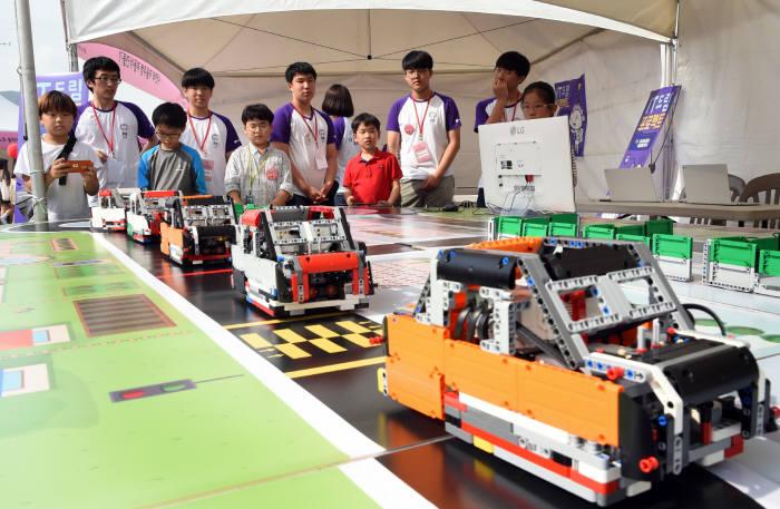 LG연암문화재단이 주최한 '영 메이커 페스티벌'에서 참가 학생들이 직접 코딩한 자율주행차 시험 주행하고 있다.
