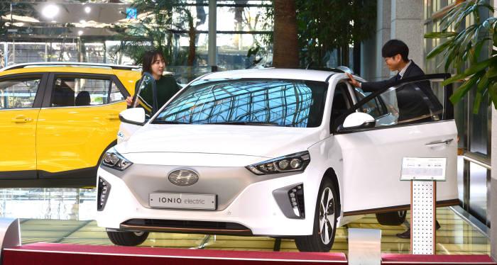 서울 서초구 양재동 현대기아자동차 본사에 전시된 '아이오닉 일렉트릭'을 방문객이 살펴보고 있다.