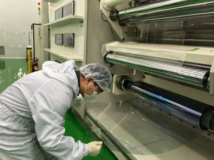 엠에스웨이 직원이 1.2미터 폭의 대면적 유연 투명전극을 코팅하는 과정을 살펴보고 있다. (사진=엠에스웨이)