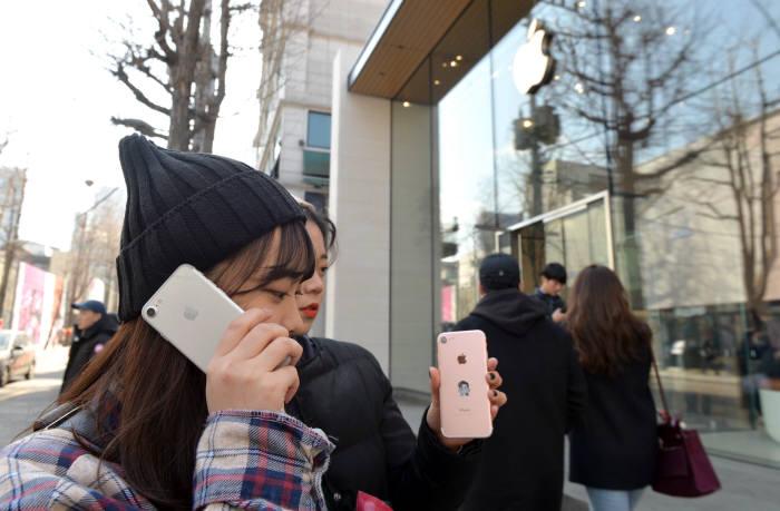 애플이 지난해 12월 14일 이후 아이폰 배터리 교체비용 10만원 정가를 낸 고객에게 차액을 돌려준다. AS와 관련해 국내 소비자에게 소극적이었던 애플이 환불정책까지 별도로 마련한 것은 배터리 게이트와 아이폰 성능저하 소송 등으로 국내 소비자들의 불만이 증가했기 때문으로 풀이된다. 연휴 서울 애플 가로수길점에서 시민이 통화를 하고 있다. 박지호기자 jihopress@etnews.com