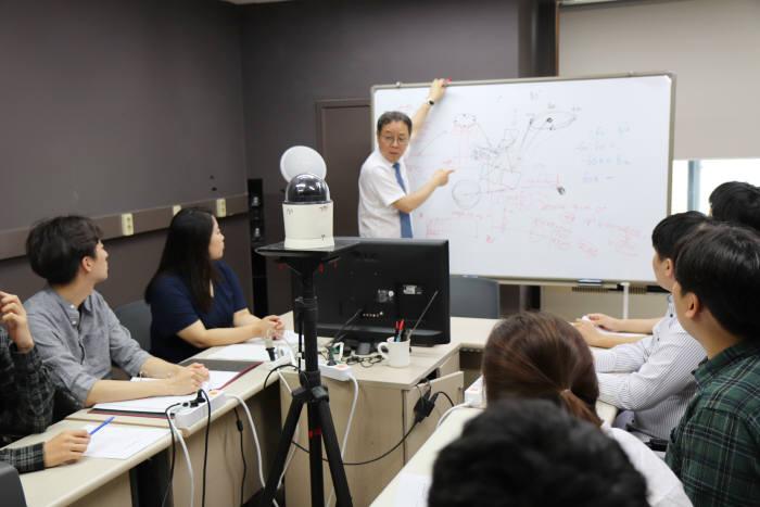 김홍국 GIST 교수가 오디오 지능 연구실에서 학생들과 AI의 청각지능 연구에 대해 얘기를 나누고 있다.