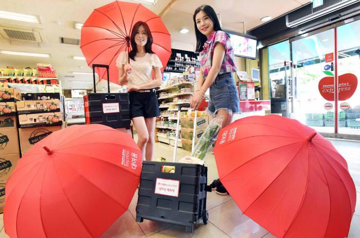 6일 홈플러스 익스프레스 옥수점에서 모델들이 대여용 우산과 쇼핑카트를 선보이고 있다.