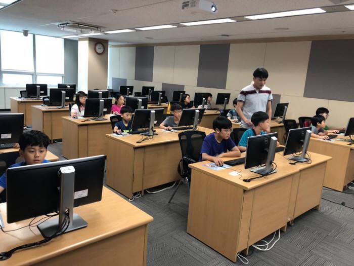 이대열 예덕초 교사가 지난주 토요일 롯데정보통신에서 열린 제5회 드림업 SW교육에서 학생에게 프로그램을 설명하고 있다.