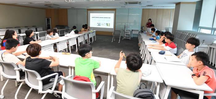 제5회 드림업 SW교육에 참여한 학생들이 AI 관련 내용을 설명듣는다.