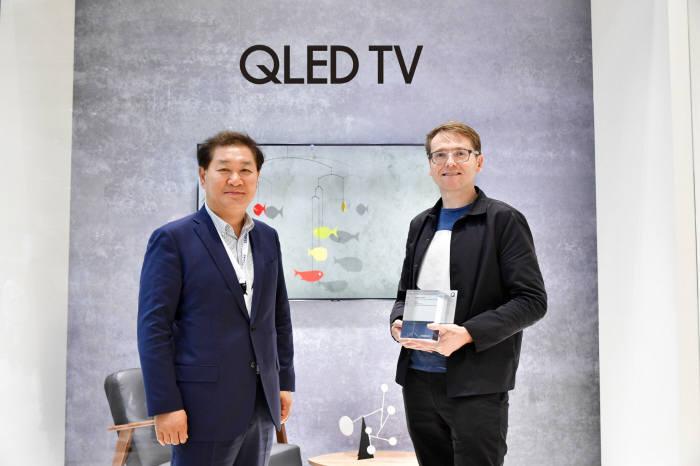 삼성전자가 8월31일(현지 시간) IFA 2018에서 QLED TV 매직 스크린 공모전 최종 우수작 시상을 진행했다. 시상식에서 이번 공모전 대상을 수상한 스위프트 크리에이티브스 매튜 커커릴 디자이너가 한종희 삼성전자 영상디스플레이사업부 사장과 기념 촬영을 하고 있다.