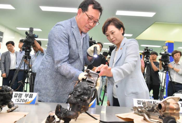 오른쪽부터 김현미 국토교통부 장관과 류도정 교통안전공단 자동차안전연구원(KATRI) 원장이 화재가 발생한 BMW 520d 결함 부품을 살피고 있다. (전자신문 DB)