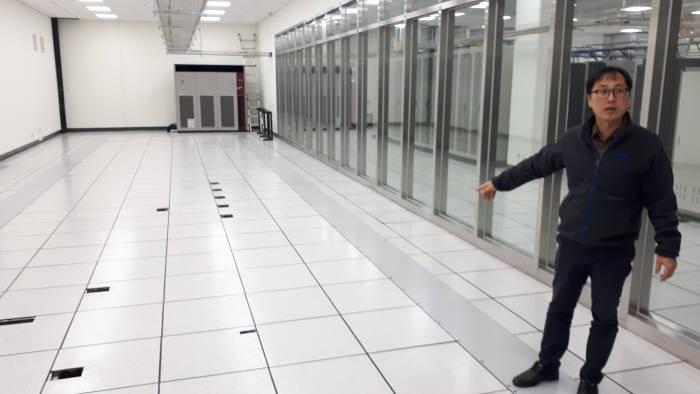 이영진 IBS 전산지원팀장이 데이터센터 슈퍼컴퓨터실 바닥에 설치된 면진이중마루를 설명하는 모습. 면진이중마루는 위에 설치될 슈퍼컴퓨터가 지진 발생시에도 안전 운용되도록 한다.