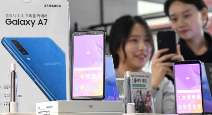 삼성전자가 내년부터 중저가형 스마트폰 갤럭시A 시리즈에 LCD 버전을 추가 출시한다. 8일 서울 광화문 휴대폰매장에서 고객이 삼성갤럭시 A7폰을 보고 있다.<br />김동욱기자 gphoto@etnews.com