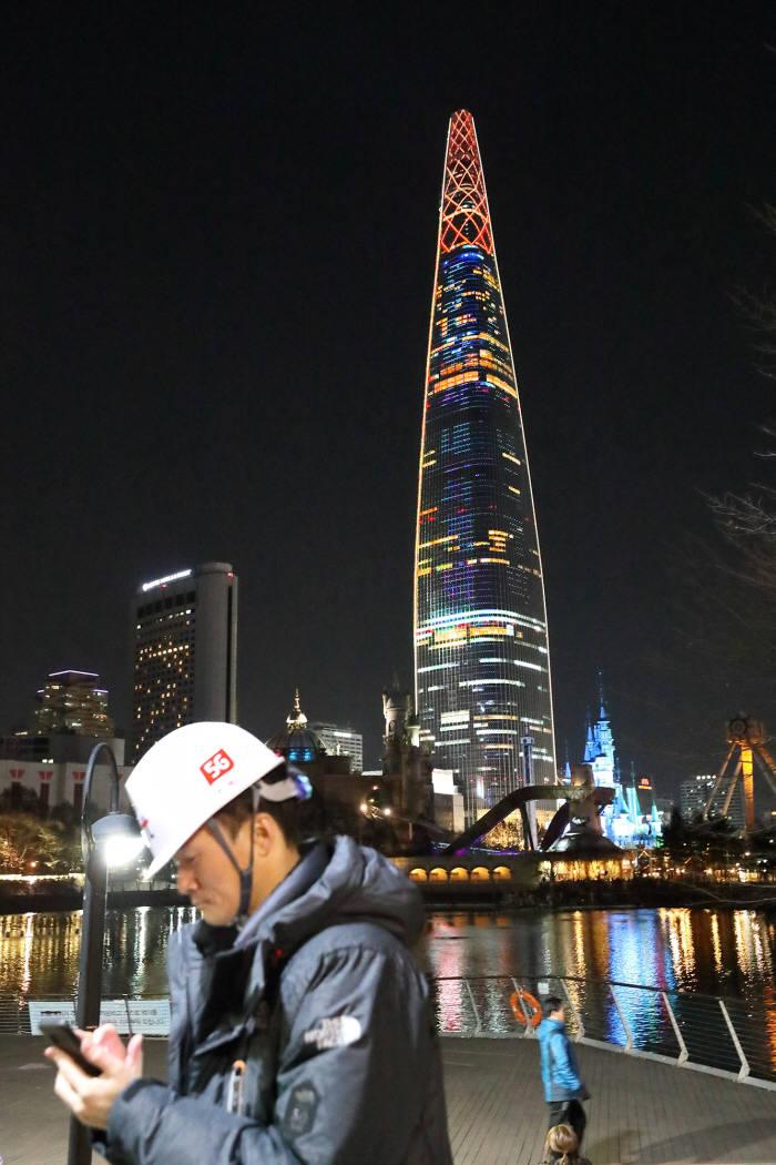 KT 임직원이 1호가입자 AI 로봇 로타가 탄생한 롯데월드 타워 주변 통신상황을 점검했다.