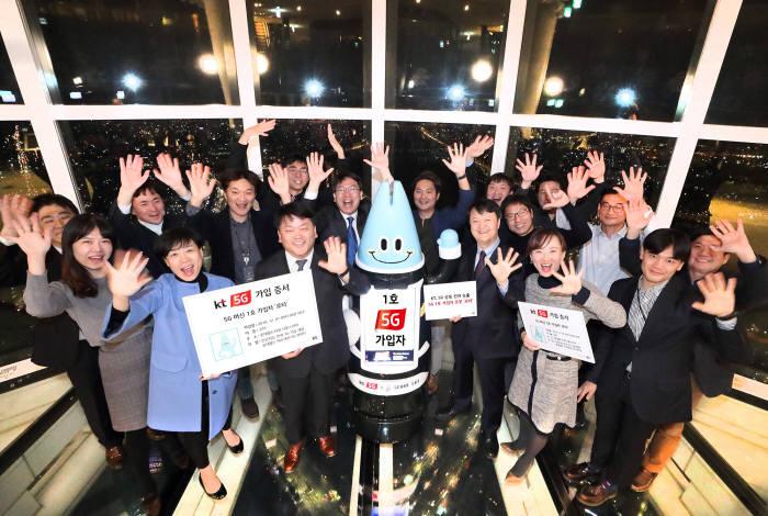 KT 임직원이 5G 전파 송출과 1호가입자 AI 로봇 로타 탄생을 기념했다.