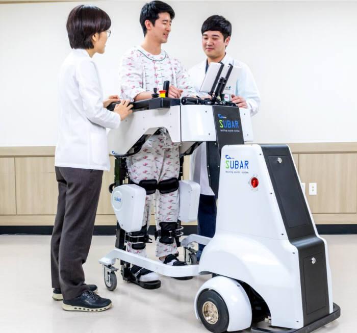 화상 환자가 한림대학교한강성심병원이 도입한 재활치료로봇을 이용해 보행 훈련을 하고 있다.