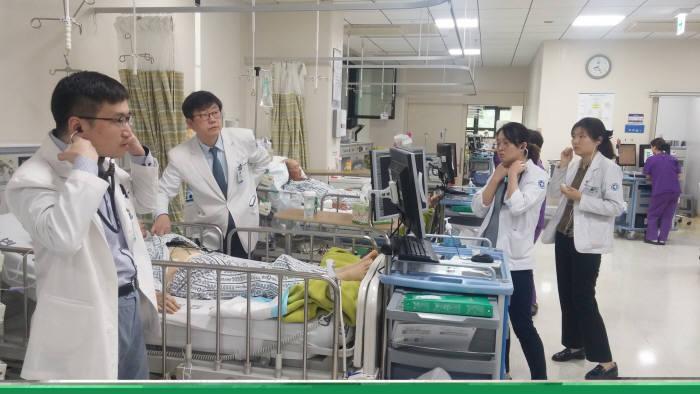 동아대병원 의료진이 무선공청 전자청진기를 이용해 환자 청진음을 공유하고 있다.