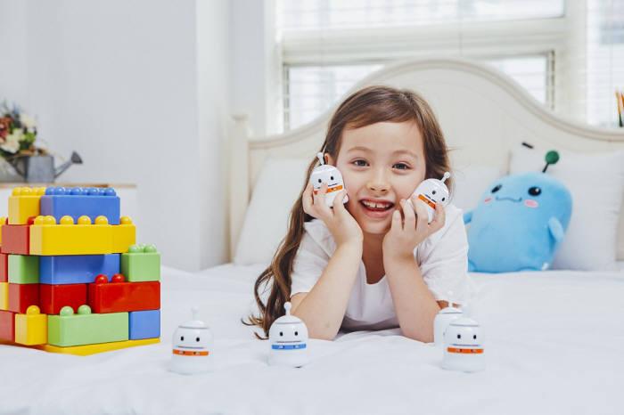시공미디어가 지난해 출시한 스마트 코딩로봇 뚜루뚜루(TRUETRUE) 광고 이미지. 어린이 모델이 뚜루뚜루를 들고 포즈를 취하고 있다. 시공미디어 제공