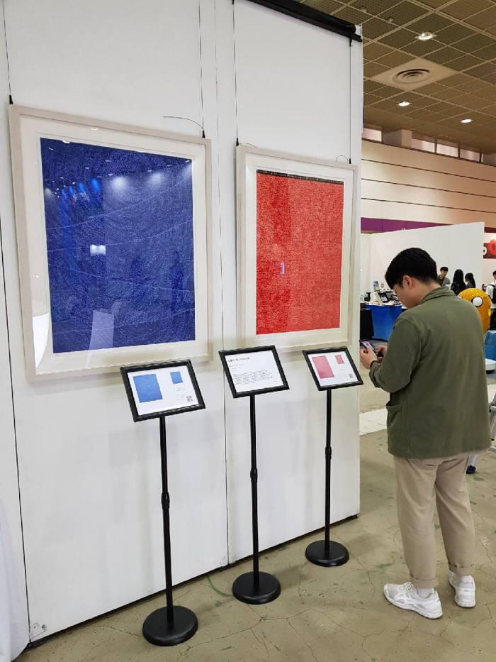 베리굿즈2019 아트앤마켓 부스에서 참관객이 스마트폰으로 작품 정보를 검색해 보고 있다.