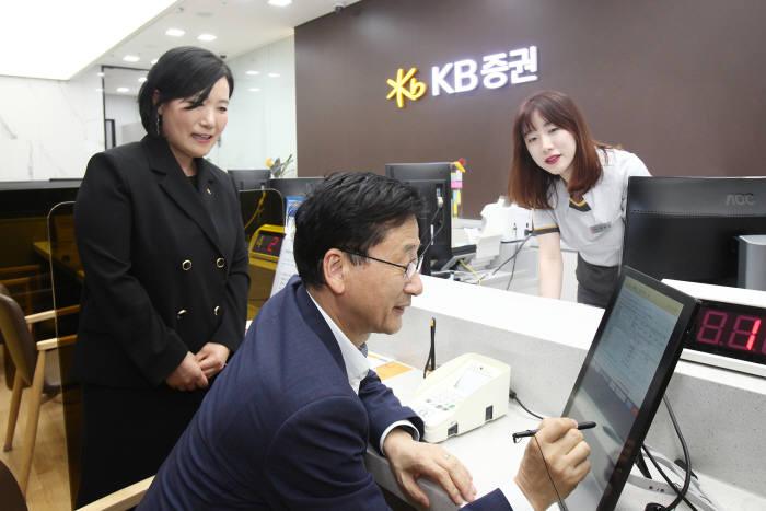 박정림 KB증권 사장(왼쪽)과 이정환 한국주택금융공사 사장(가운데)이 27일 KB증권 여의도 영업부를 방문해 디지털창구를 통해 MBS 매수를 하고 있다.