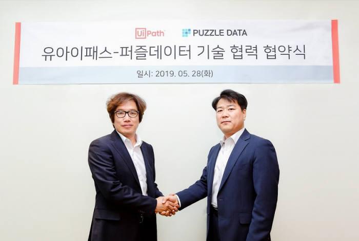 장은구 유아이패스코리아 대표(왼쪽)와 김영일 퍼즐데이터 대표가 협약체결 후 기념 사진을 촬영하고 있다. 유아이패스코리아 제공