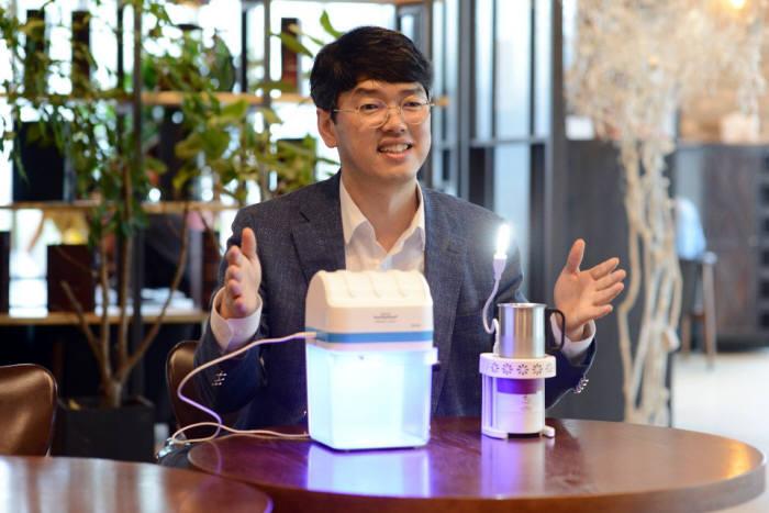박은현 쉐어라이트 대표가 촛불의 열 에너지로도 LED 조명을 켤 수 있는 쉐어라이팅(오른쪽), 수동으로 전력을 생산해 UVC LED 물 살균을 할 수 있는 퓨리라이트를 소개하고 있다.