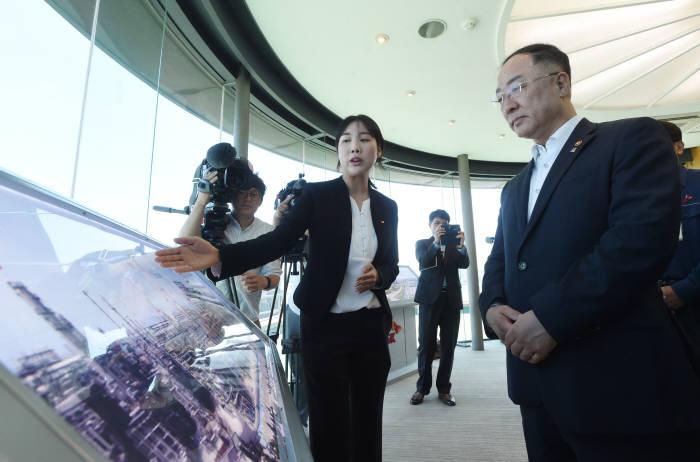홍남기 경제부총리 겸 기획재정부 장관이 SK이노베이션 울산CLX 관계자로부터 설명을 듣고 있다.