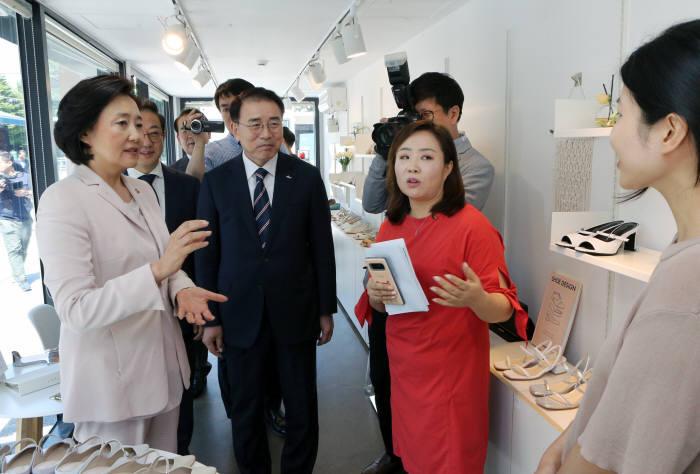 박영선 장관(앞줄 왼쪽 첫번째)과 조용병 회장(앞줄 왼쪽 두번째)이 예비창업 사업모델에 대해 설명을 듣고 있다.