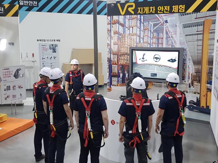 롯데하이마트 물류센터 직원들이 VR 지게차 안전 교육을 체험하고 있다.