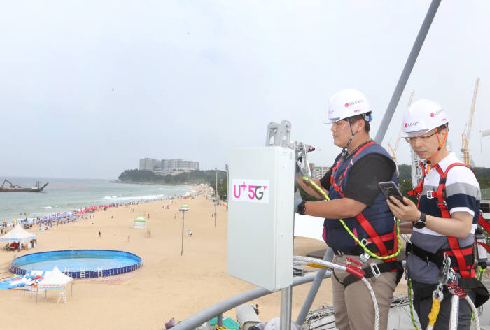 LG유플러스가 여름 휴가 시즌을 맞아 해수욕장, 관광지 등 전국 주요 휴가지에서 U+5G를 즐길 수 있도록 5G 기지국 구축에 박차를 가한다. LG유플러스 직원이 강원도 속초시 속초해수욕장에서 5G 기지국을 설치하고 최적화 작업을 하고 있다.