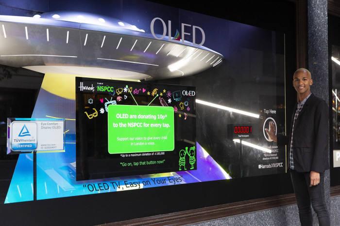 LG디스플레이가 영국 해롯백화점 1층 쇼윈도에 설치한 OLED 체험형 기부캠페인에 방문객이 손바닥 모양을 클릭해 참여하고 있다. (사진=LG디스플레이)