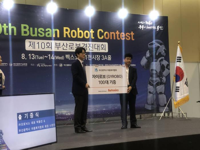 박용진 오토닉스 대표(왼쪽)와 나영찬 부산아동복지협회장이 자이로봇 100대를 기증식 후 기념촬영했다.