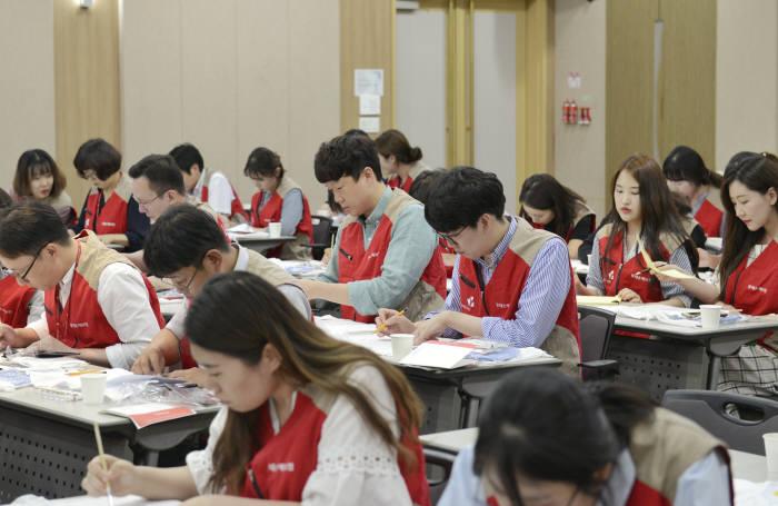 롯데손해보험 임직원들이 지난 13일 서울 중구 본사에서 기후난민 어린이들에게 전달할 희망 티셔츠를 직접 만들고 있다.