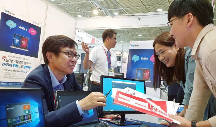 이창열 브이엠솔루션 대표(왼쪽)가 2019 국제병원의료산업박람회에서 관람객에게 논리적 망분리 솔루션 브이엠포트(VMFort)를 소개하고 있다.