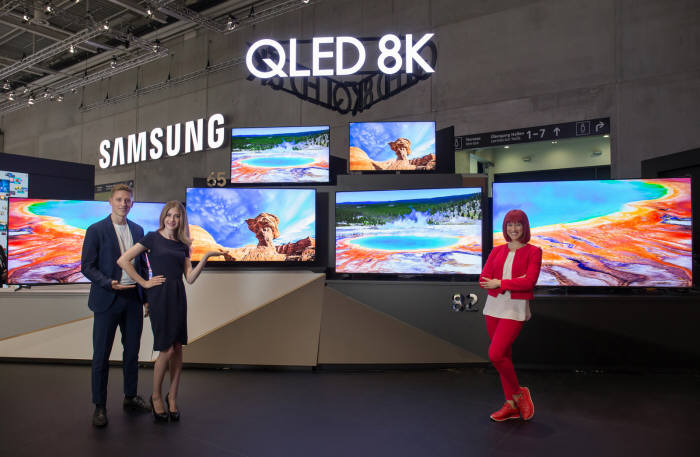 IFA 2019 공식 모델(우측)과 삼성전자 모델들이 IFA 2019 삼성전자 전시장에서 55형부터 98형까지 QLED 8K TV. 풀 라인업을 소개하고 있다.